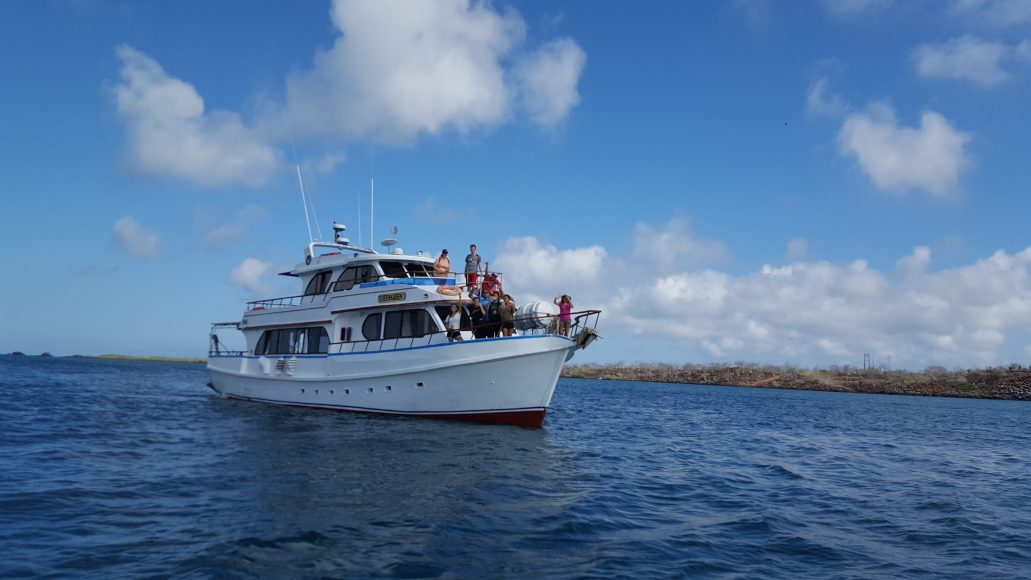 A yacht sails the group between the Galápagos islands.