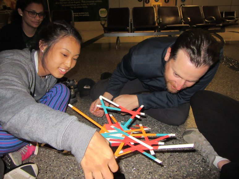 The group plays an intense game of stick stack at the LAX airport.